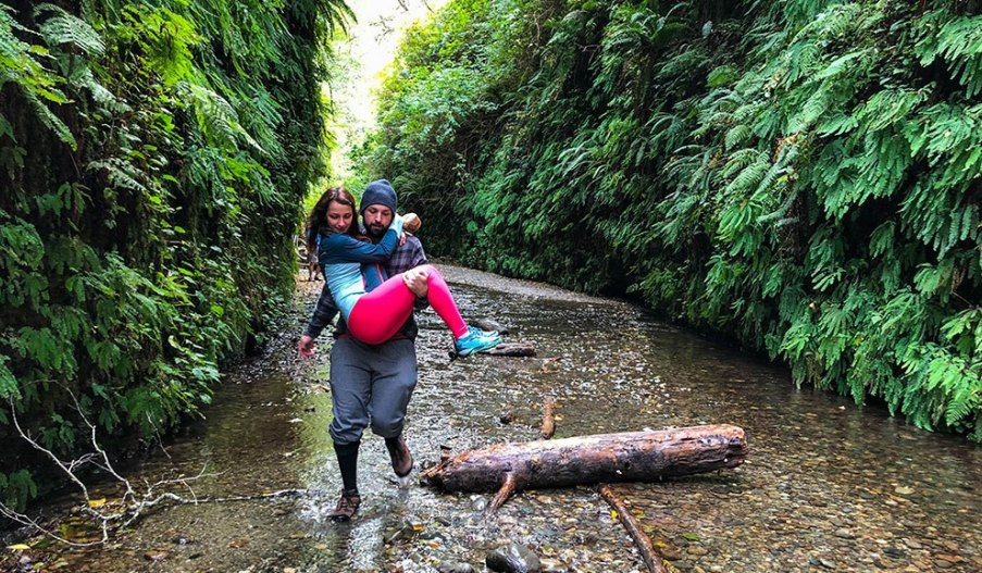 A very gallant gentleman carries his girl over the water in Fern Canyon